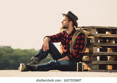 Farmer enjoy view from his farm. Romanticism of western culture. Farmer in hat sit relax. Peaceful mood. Watching sunset. Farmer cowboy handsome man relaxing after hard working day at ranch.