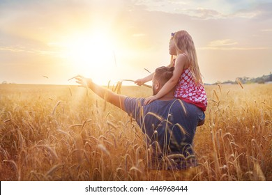 Farmer Father with his daughter balancing on his shoulder with their arms outstretched in a wheat field.