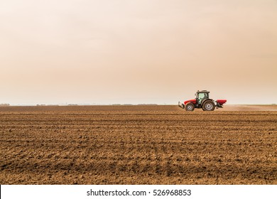 Farmer fertilizing arable land with nitrogen, phosphorus, potassium fertilizer
