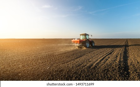 Farmer fertilizing arable land in spring