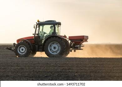 Farmer fertilizing arable land in spring