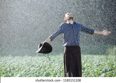 The farmer in the hat is enjoying the rain. Young man getting wet under the rain in summer.
