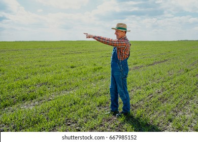 A farmer in a hat stands on his broad field and points his finger on the horizon