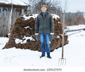 farmer in heap of fertilizer on a winter day