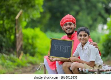 farmer with his child showing shiksha word writing in marathi language on chalkboard