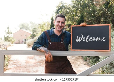 Farmer holding a blackboard welcoming sign