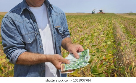 Farmer holding Euro banknote with harvest in soy bean field in background