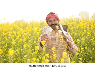 Farmer holding Indian Rupee notes in field