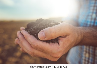 Farmer holding pile of arable soil, male agronomist examining quality of fertile agricultural land, close up with selective focus