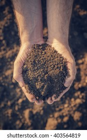 Farmer holding pile of arable soil and examining its quality, close up of hands.
