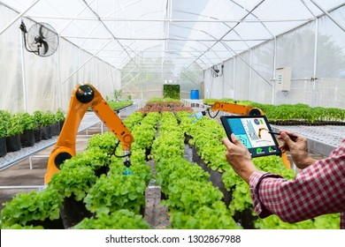 Farmer holding a tablet smart robotic harvest in agriculture futuristic robot automation to work technology increase efficiency