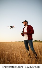Farmer holds remote controller with his hands while quadcopter is flying on background. Drone hovers behind the agronomist in wheat field. Agricultural new technologies and innovations. Back view
