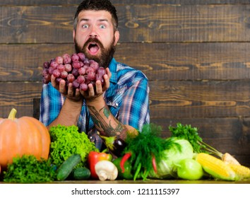 Farmer with homegrown harvest on table. Farmer proud of harvest vegetables and grapes. Man bearded holds grapes wooden background. Vegetables organic harvest. Farming and harvesting concept.