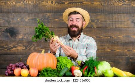 Farmer with homegrown harvest. Farmer rustic villager appearance. Man cheerful bearded farmer hold horseradish wooden background. Grow organic crops. Farmer straw hat presenting fresh vegetables.