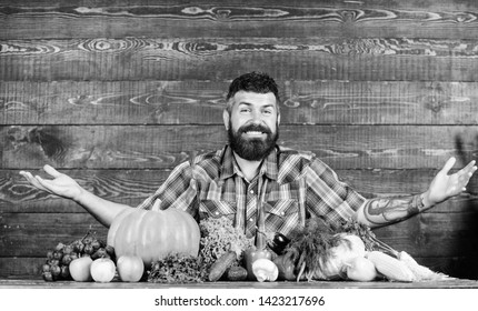 Farmer with homegrown vegetables. Vegetables organic harvest. Farmer rustic style guy. Vegetarian lifestyle concept. Natural foods. Man bearded farmer harvest wooden background. Welcome to my farm.