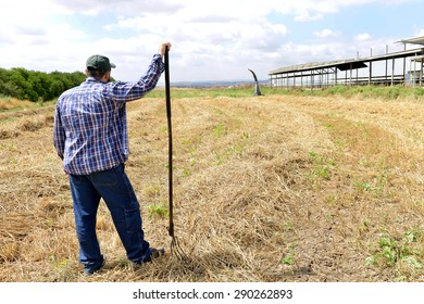 Farmer leaning on his fork and watching his field