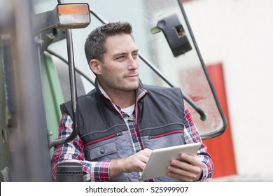 Farmer leaning on the tractor using a digital tablet