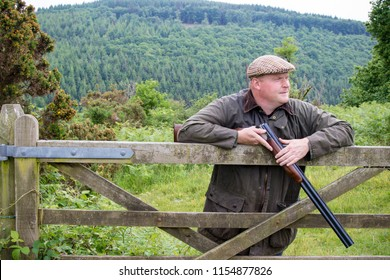 Farmer leaning on a wooden gate holding a broken shotgun