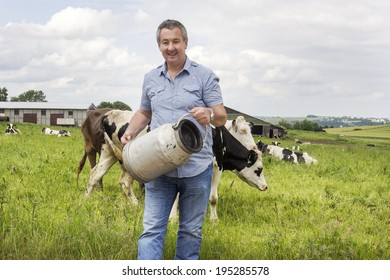 Farmer with milk churns in front of his cows
