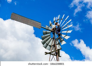 Farmer on his farm up on a windmill fixing the pump