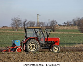 A farmer on a red tractor with a seeder sows grain in plowed land in a private field in the village area. Mechanization of spring field work. Farmer's everyday life. relief of human labor.