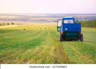 The farmer on the tractor collects the hay cut in the field in bales for storage for the winter in the barn on the farm