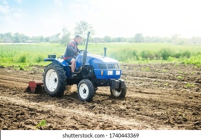 A farmer on a tractor works on the field. Growing crops in a small agricultural family enterprise. Small business support. Farming and agriculture. Cultivation technology equipment. Food production