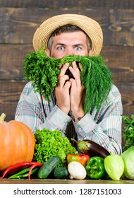 Farmer with organic vegetables. Just from garden. Grocery shop concept. Buy fresh homegrown vegetables. Excellent quality vegetables. Man with beard proud of his harvest vegetables wooden background.