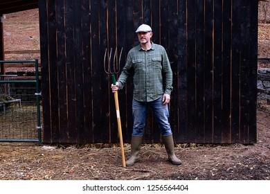 A farmer with pitchfork against old barn.