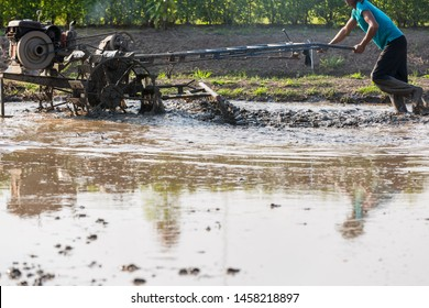 Farmer ploughing field using small tractor,kubota tractor,agricultural machinery,Thailand