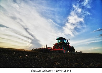 Farmer plowing field in tractor with seed bed