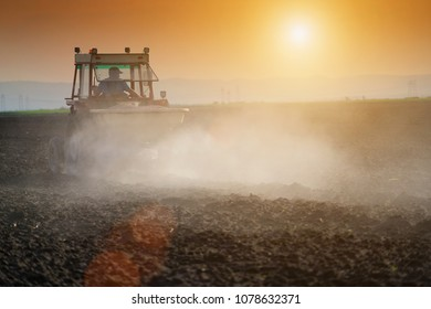 Farmer plowing field in tractor with seed bed at sunset