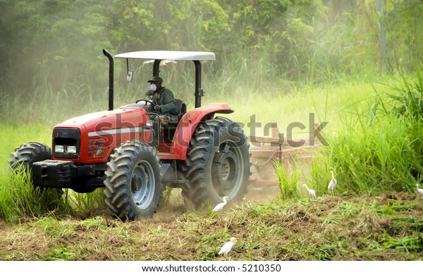 Farmer prepares the land for crops, in a very dusty environment