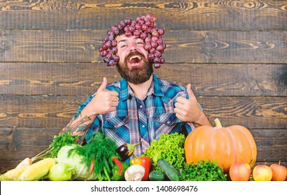 Farmer proud of grapes harvest. Fresh organic harvest. Grapes from own garden. Farming concept. Farmer bearded guy with homegrown harvest grapes put on head. Man hold grapes wooden background.