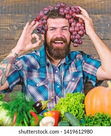 Farmer proud of grapes harvest. Fresh organic harvest. Grapes from own garden. Farming concept. Man hold grapes wooden background. Farmer bearded guy with homegrown harvest grapes put on head.