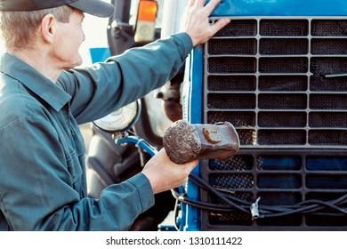 Farmer repairing tractor. Male hand holding big hammer, sledgehammer.