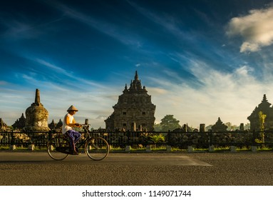 Farmer riding bike at road with temple background with blue sky: Plaosan Temple, Central Java, Indonesia - August 2018