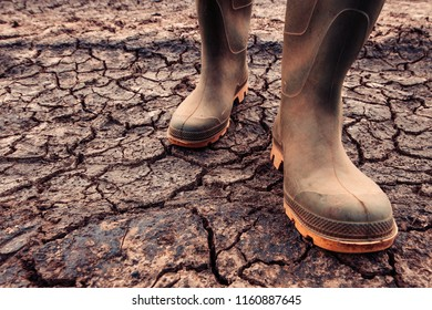 Farmer in rubber boots standing on dry soil ground, global warming and climate change is impacting crops growing and yield