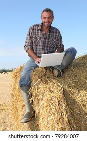 farmer seated on straw bale and doing computer