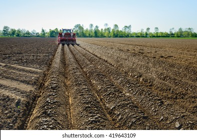 Farmer seed potatoes in a Dutch field of clay soil with the aid of a tractor coupled to the 4-row combi-planting machine which at the same time also forms the ridges.