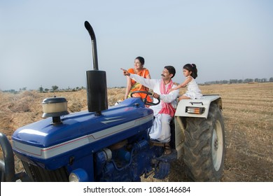 Farmer showing something to family while driving a tractor