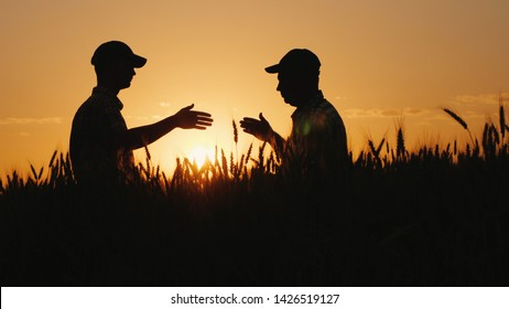 The farmer signs a contract on the field, business partners shake hands. Agribusiness deal