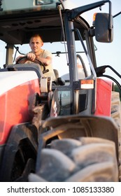 Farmer sitting in his tractor at sunrise
