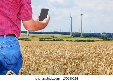 Farmer with smartphone in cornfield
