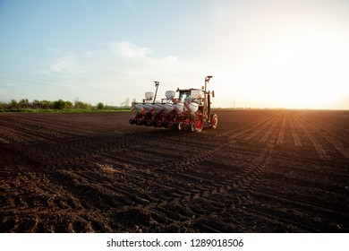 Farmer sowing crops at field with tractor.