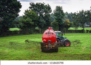 Farmer spraying liquid manure by use of a slurry tanker on a green meadow.
