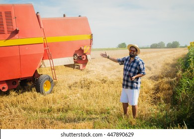 Farmer standing beside a harvester on a crop field.