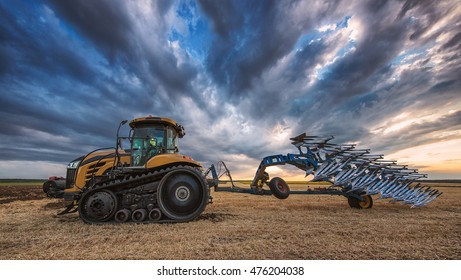 Farmer in Tractor with Plough, Plowing in a Field