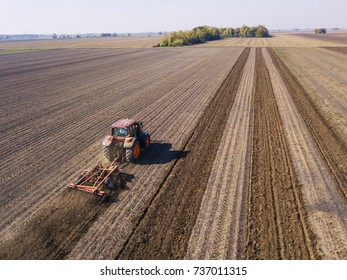 Farmer in tractor preparing agricultural soil for sowing