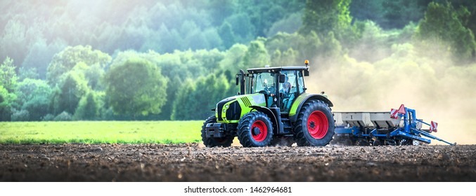Farmer in tractor is preparing ground or soil with cultivator for seeding activities at spring season. agriculture works and farmland. Wide banner or panoramatic photo.